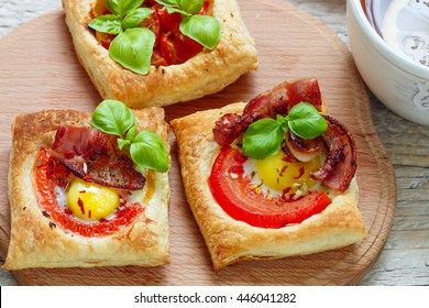 Open pies of puff pastry with quail egg, tomatoes, bacon and Basil. Breakfast. Selective focus