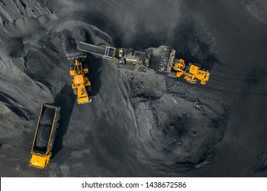Open pit mine, excavator loads coal to crushing machine, chopper and sorting, top view aerial drone.