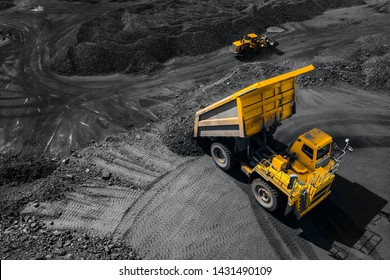 Open pit mine industry, big yellow mining truck for coal, top view aerial drone.