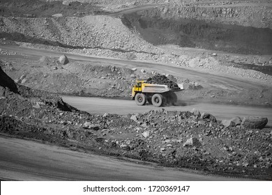 Open pit mine industry. Yellow mining truck for coal moves along dusty quarry road.