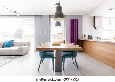 Open plan apartment of family living-space with wooden kitchen countertop, purple radiator, communal table with turquoise chairs and spacious living room with beige couch