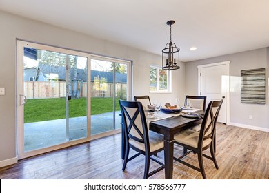 Open plan dining room interior with light wood floors showcases a black dining table set and sliding doors to fenced backyard. Northwest, USA