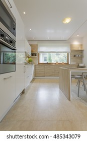Open plan kitchen area surrounded by cupboards with oven and fridge, with table and minimalistic chair and with the window