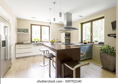 Open plan kitchen area with kitchen units and amenities around and the worktop surrounded by chairs in the middle of the bright kitchen space