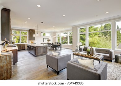 Open plan kitchen equipped with high-end appliances opens to the dining room and the great room with lots of natural light provided by white framed windows. Northwest, USA