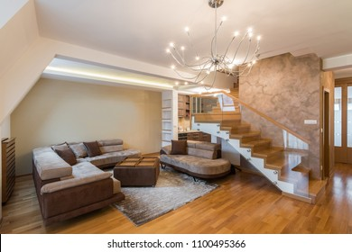 Open plan living room interior in luxury loft apartment with stairs
