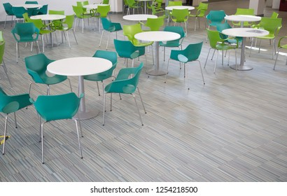 Open plan rest, common or cafe area in a school college or work place. Green and white plastic chairs and tables. Many in a room. UK