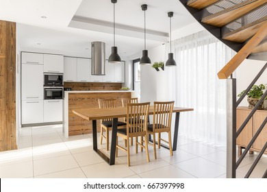 Open plan of white kitchen and wooden dining room