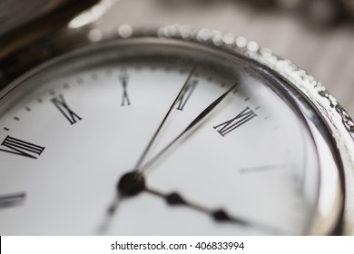 open pocket watches lie on a light wooden table background, arrow on the clock, arrows on pocket watches show time of day, dial with roman numerals