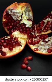 open pomegranate and scattered seeds on black slae trivet