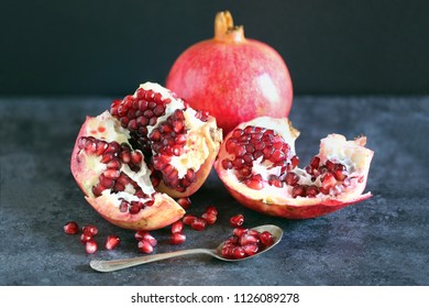 Open pomegranate showing the red jewel like seeds. Includes an out of focus whole Pomegranate in the background and a small spoon in the foreground with several seeds on it.