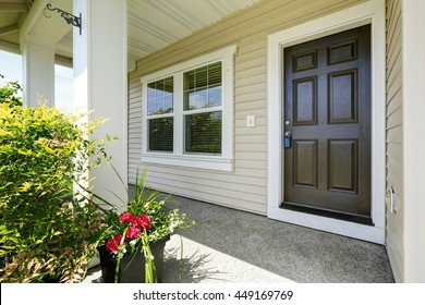 Open porch with concrete floor, column and entrance brown door. Decorated with hanging lantern light and pots with flowers