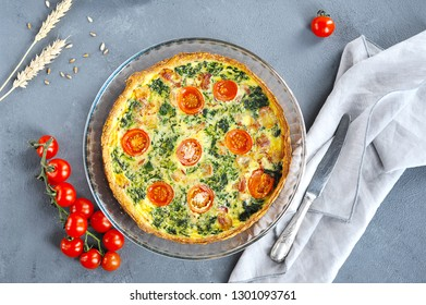 Open quiche pie with spinach and bacon. In the frame of a knife, cloth napkin, cherry tomatoes. Gray background. View from above. Close-up.