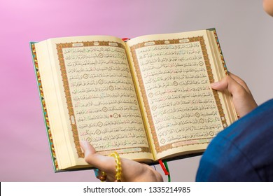 The open Qur'an is held by the hand of Indonesian muslim, holding the prayer beads (tasbih). The Qur'an is the holy book of Islam.