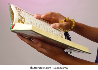 The open Qur'an is held by the hand of Indonesian muslim, holding the prayer beads (tasbih). The Qur'an is the holy book of Islam. Indonesian muslim.