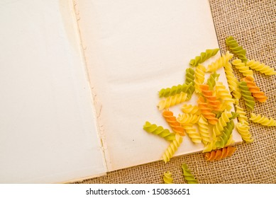Open recipe book with blank page and colorful pasta, top view
