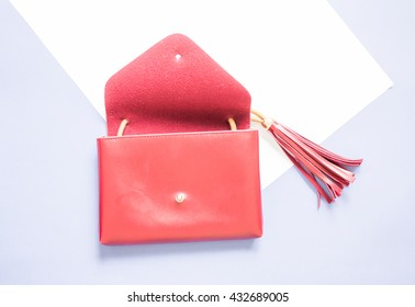 open red clutch bag design with tassel on white and blue background.