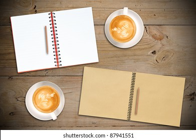 Open Red Notebook, Open Vintage Sketch Book, Penils with two cups of Latte on Old Wooden Table - Shutterstock ID 87941551