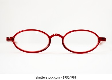 Open red reading glasses isolated on white seen from front