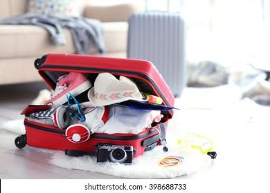 Open red suitcase on the floor, close up