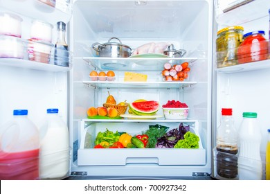 Open refrigerator filled with food.