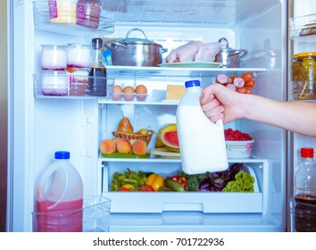 Open refrigerator filled with food. Hands holding a bottle of milk