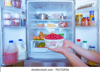Open refrigerator filled with food. Hands holding a box of raspberries