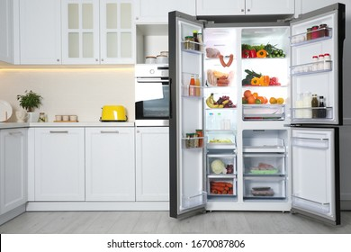 Open refrigerator filled with food in kitchen