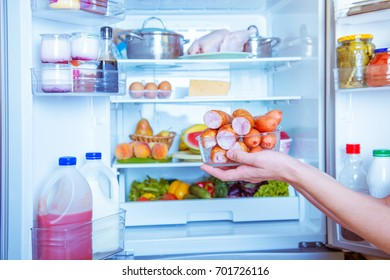 Open refrigerator filled with food.hands holding sausage