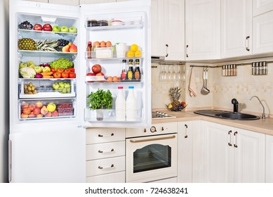 Open refrigerator filled with fresh fruits, vegetables and milk products in kitchen room, healthy nutrition lifestyle concept