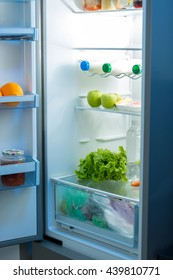 Open refrigerator full of food on kitchen at night