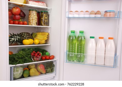 Open refrigerator full with some kinds of food and drinks