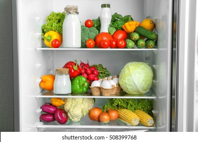 Open refrigerator full of vegetables and dairy products