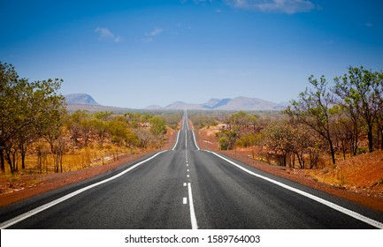 The open road in Kimberly, Western Australia. Straight single lane asphalt road stretching into the distance with mountains in the background. Holiday adventure.