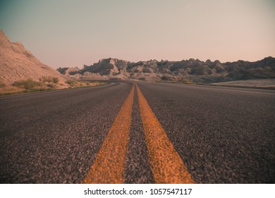 Open Road Leading to Adventure through the Mountainous Landscape of the Badlands in South Dakota