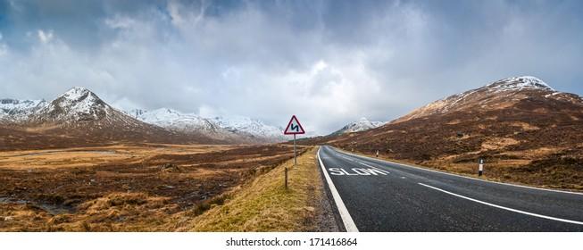 Open road leading through the dramatic Scottish Highlands of Glen Coe, Scotland.