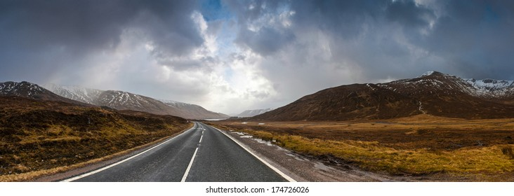 Open road leading through the Scottish Highlands of Glen Coe, snowcapped mountains and dramatic storm broken sky.