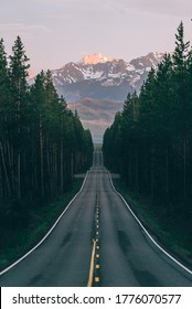An open road leads to the Grand Teton's mountain range, rising in the distance beyond a thick pine forest. The last rays of sunlight shine on the mountain. Photo shot vertically to include more road.  - Shutterstock ID 1776070577