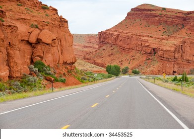 Open road progressing through red rock mountains.