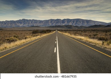 Open road running straight over a beautiful landscape in South Africa with majestic mountains in the distance.