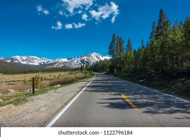Open road stretching to snow covered Mammoth Peak, Yosemite