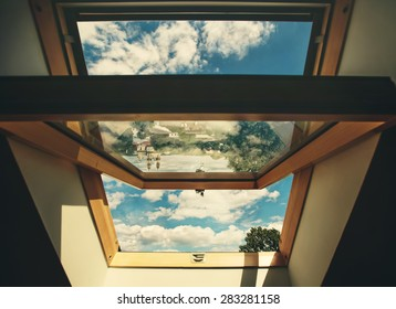 Open roof window skylight with old European city reflection, the chapel and cloud sky