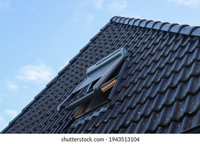 Open roof window in velux style with black roof tiles