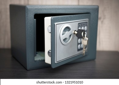 open safe with keys on the door on a light background