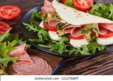 open sandwich - italian piadina with mozzarella, tomato, salami slices, grilled zucchini and arugula on a black plate with ingredients on a cutting board, view from above, close-up