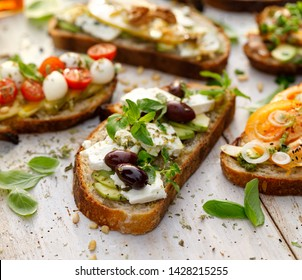 Open sandwich made of slices of sourdough bread with avocado, feta cheese, kalamata olives, olive oil and oregano on a wooden white table, close-up. Vegetarian food