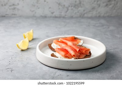open sandwich with salmon, cream cheese and rye bread in a white plate on a gray concrete background