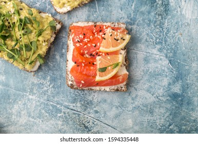 Open sandwiches with avocado, red fish, micro greenery on a blue stone background. Close-up