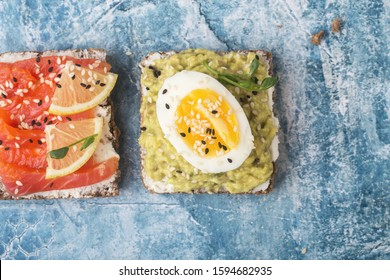 Open sandwiches with avocado, red fish on a blue stone background. Close-up
