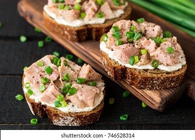 Open sandwiches with cottage cheese, canned tuna and green onions on black wooden background. Selective focus.